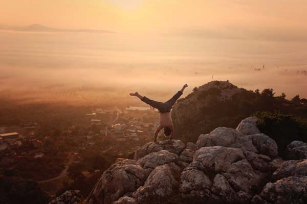 Doing a handstand on a mountain top