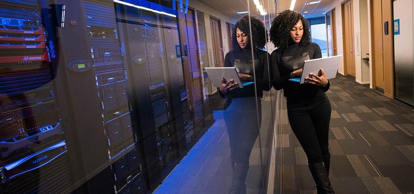 A woman using a laptop computer, standing near servers - Web Developer Skills
