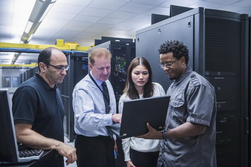 Colleagues working together in server room