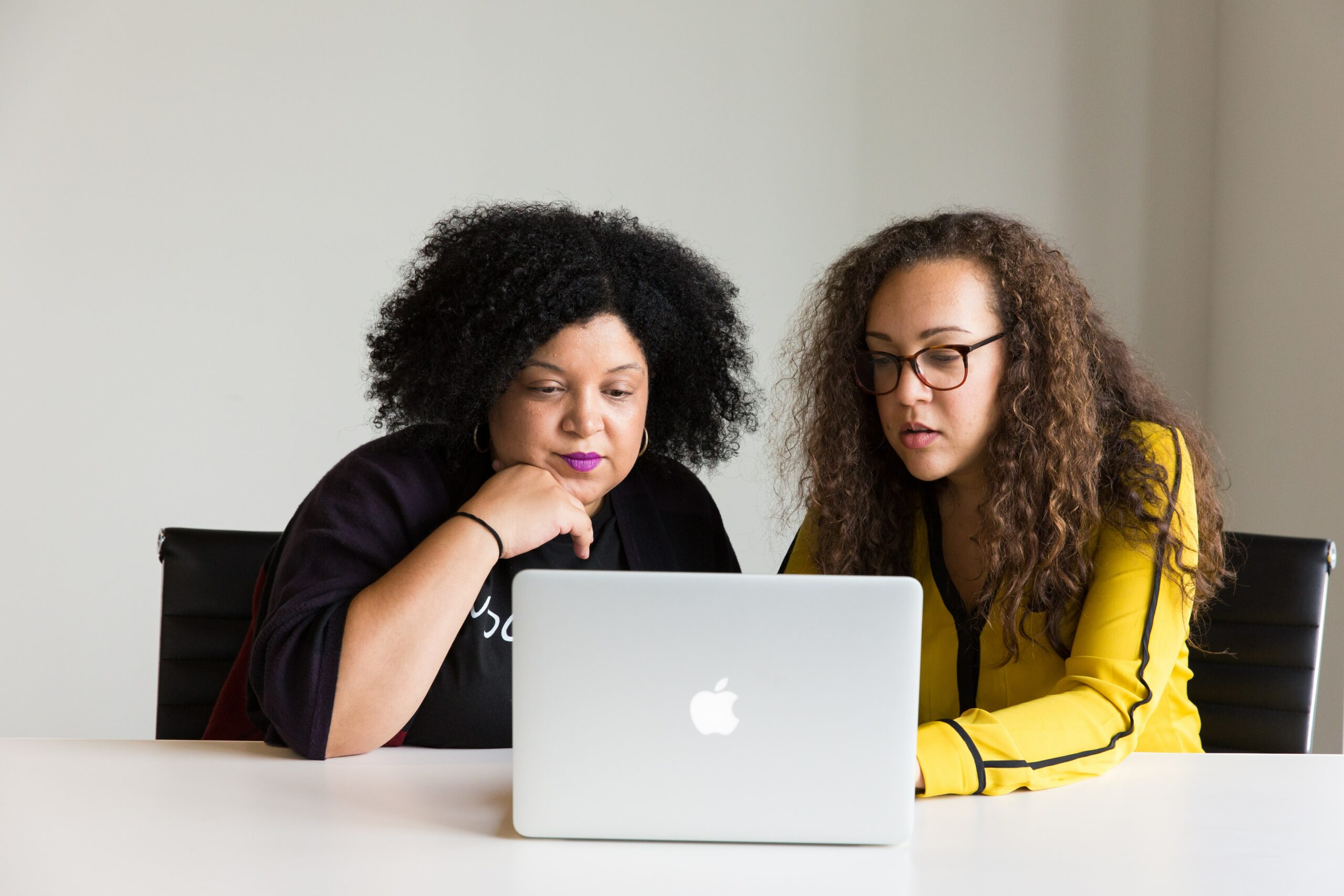 Two women talking about something on a computer screen