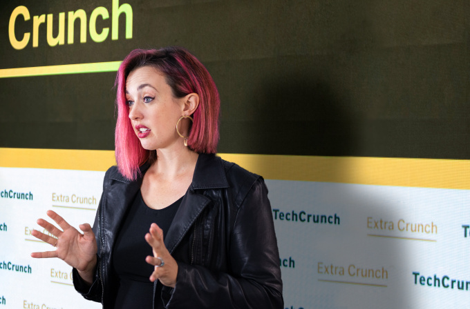 A composite image of immigration law attorney Sophie Alcorn in front of a background with a TechCrunch logo.
